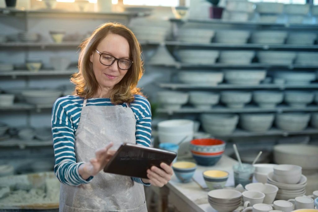 Smiling White woman with glasses working in iPad in front of dozens of clay pots